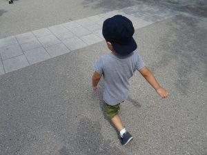 歩く帽子をかぶった子ども